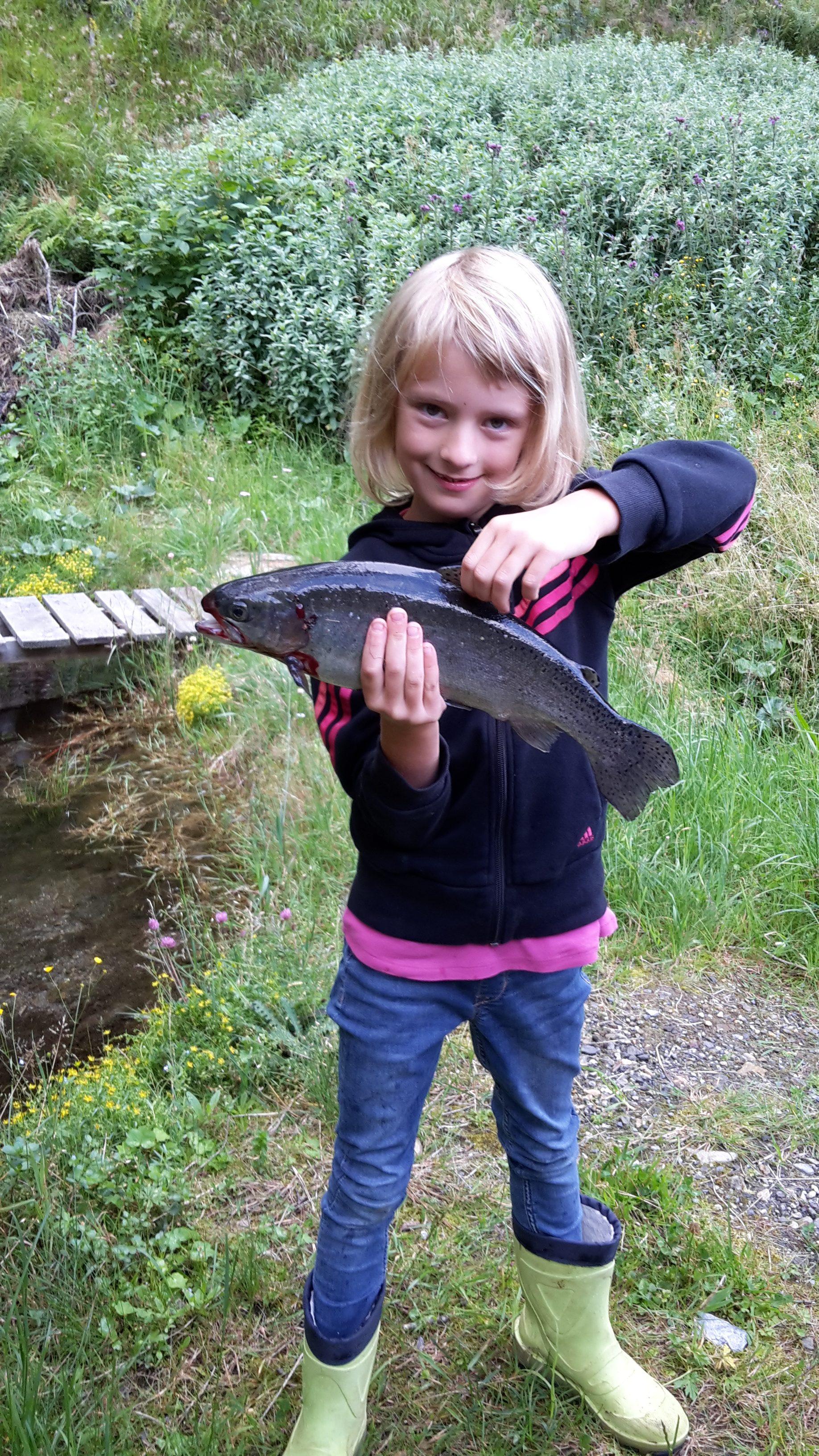 Anna mit der selbst geangelten Forelle bei den Fischteichen auf der Alm